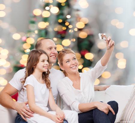 familias jovenes: familia, d�as de fiesta, la tecnolog�a y la gente concepto - sonriendo madre, padre y ni�a haciendo Autofoto con c�mara sobre las luces del �rbol de Navidad de fondo