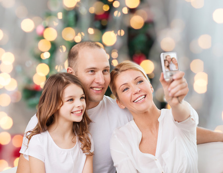 family, holidays, technology and people concept - smiling mother, father and little girl making selfie with camera over christmas tree lights background photo