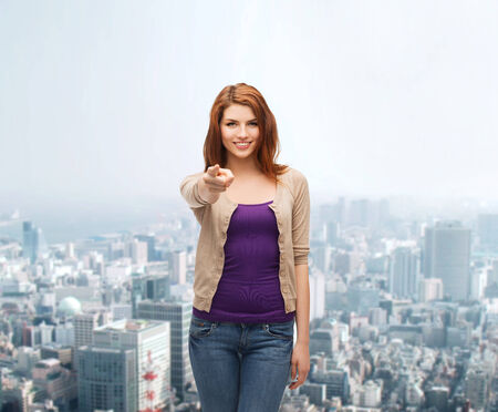 business, gesture and people concept - smiling teenage girl in casual clothes pointing finger on you over city background photo