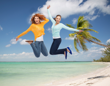 summer vacation, travel, freedom, friendship and people concept - smiling young women jumping in air over tropical beach background photo