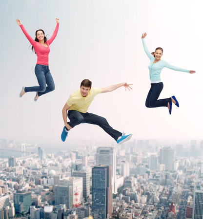 flying woman: happiness, freedom, friendship, movement and people concept - group of smiling teenagers jumping in air over city background Stock Photo