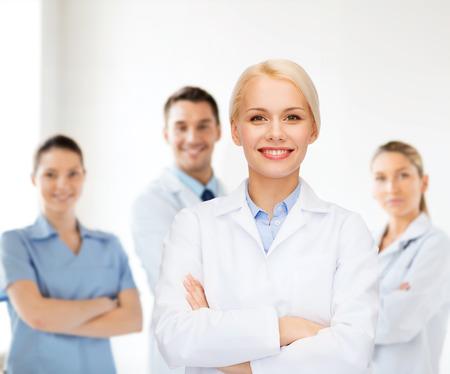 의료 및 의학 개념 - 병원에서 의료진의 그룹을 통해 여성 의사를 웃 고