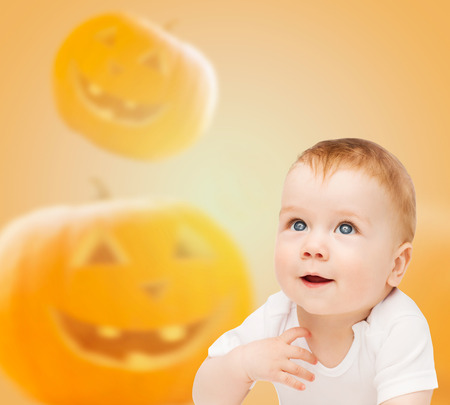 holidays, childhood, happiness and people concept - smiling baby over pumpkins background photo