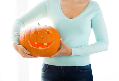 holidays, halloween, decoration and people concept - close up of woman with pumpkins at home photo
