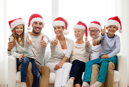 family, happiness, generation, holidays and people concept - happy family in santa helper hats sitting on couch and showing thumbs up gesture at home photo
