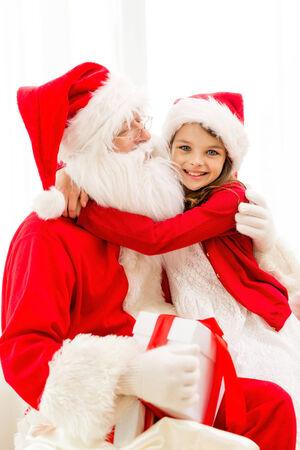 vakantie, kerstmis, geluk en mensen concept - lachende meisje met geschenk doos omarmen Kerstman thuis