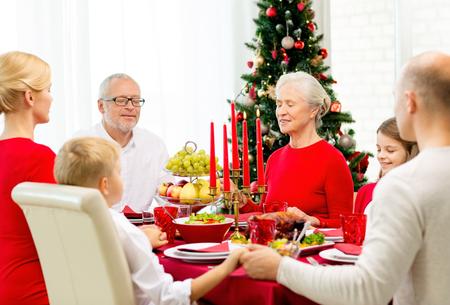 familia orando: familiares, vacaciones, generación, navidad y concepto de la gente - sonriendo familia cenando y orando en casa Foto de archivo