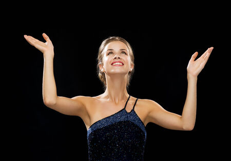 people, happiness, holidays and glamour concept - smiling woman raising hands and looking up over black background Stock Photo