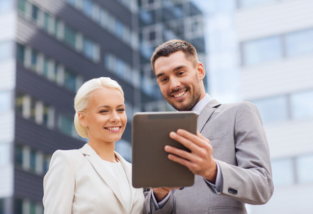 computer applications: business, partnership, technology and people concept - smiling businessman and businesswoman with tablet pc computer over office building Stock Photo
