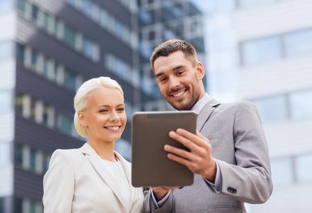 zaken, partnerschap, technologie en mensen concept - glimlachende zakenman en zakenvrouw met een tablet pc computer op kantoor gebouw Stockfoto