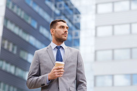 latin man: business, hot drinks and people and concept - young serious businessman with paper coffee cup over office building