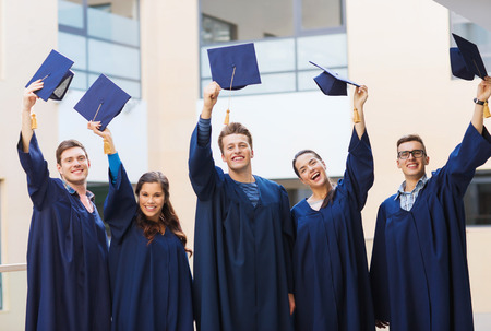 education, graduation and people concept - group of smiling students in gowns waving mortarboards outdoors photo