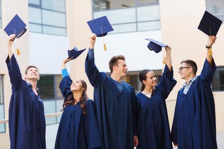 graduacion de universidad: la educación, la graduación y concepto de la gente - grupo de estudiantes sonrientes en vestidos ondeando birretes al aire libre