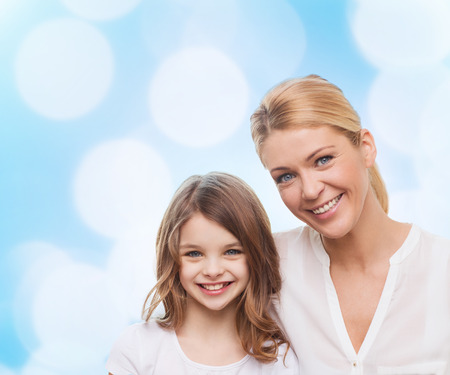 cute teen girl: family, childhood, happiness and people - smiling mother and little girl over blue lights background