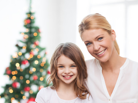 family, childhood, holidays and people - smiling mother and little girl over living room and christmas tree background