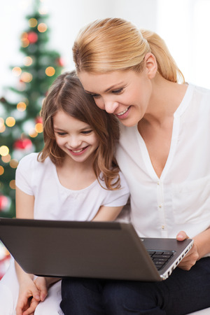 family, childhood, holidays, technology and people - smiling mother and little girl with laptop computer over living room and christmas tree background photo