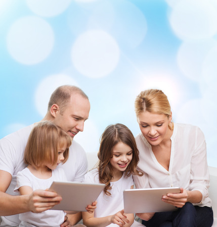 family, holidays, technology and people - smiling mother, father and little girls with tablet pc computers over blue lights background photo