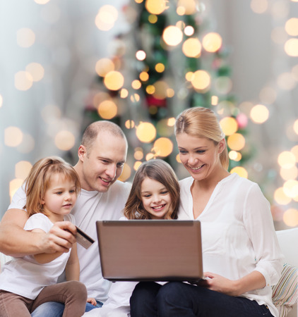 family, holidays, shopping, technology and people - happy family with laptop computer and credit card over christmas lights tree background photo