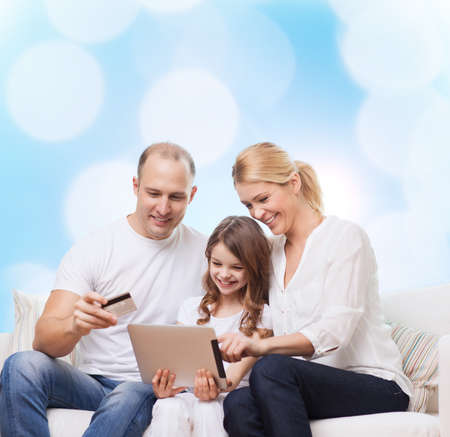 family, holidays, shopping, technology and people - smiling family with tablet pc computer and credit card over blue lights background photo