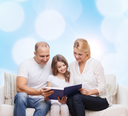 family, childhood, holidays and people - smiling mother, father and little girl reading book over blue lights background photo