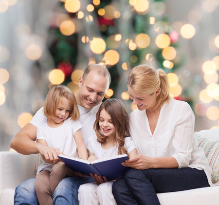 beautiful preteen girl: family, childhood, holidays and people - smiling mother, father and little girls reading book over living room and christmas tree lights background