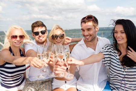 concept van vakantie, reizen, zee, vriendschap en mensen - lachende vrienden met glazen champagne op jacht