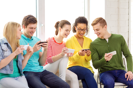 free time: education, school and technology concept - smiling students with smartphone texting at school Stock Photo