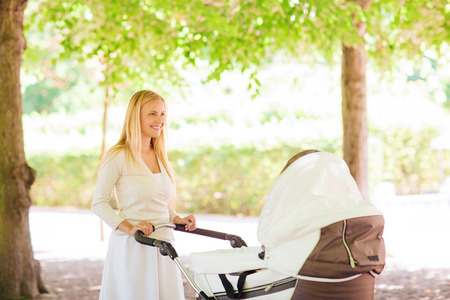 family, child and parenthood concept - happy mother with stroller in park photo