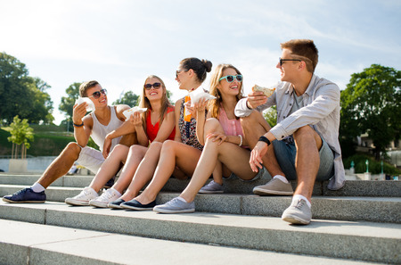 friendship, leisure, summer and people concept - group of smiling friends in sunglasses sitting with food on city square photo