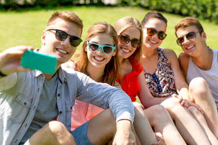friendship, leisure, summer, technology and people concept - group of smiling friends with smartphone making selfie in park photo