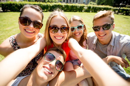 group: friendship, leisure, summer, technology and people concept - group of smiling friends making selfie with smartphone, camera or tablet pc in park Stock Photo