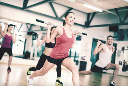 pesas: fitness, deporte, entrenamiento, gimnasio y estilo de vida concepto - grupo de gente sonriente de trabajo con pesas en el gimnasio Foto de archivo