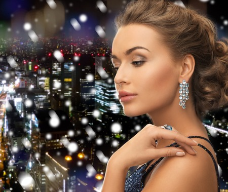 people, holidays, christmas and glamour concept - beautiful woman in evening dress wearing ring and earrings over snowy night city background photo