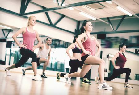 fitness, sport, szkolenia, siłownia i koncepcja życia - grupa uśmiechniętych ludzi wykonujących w siłowni
