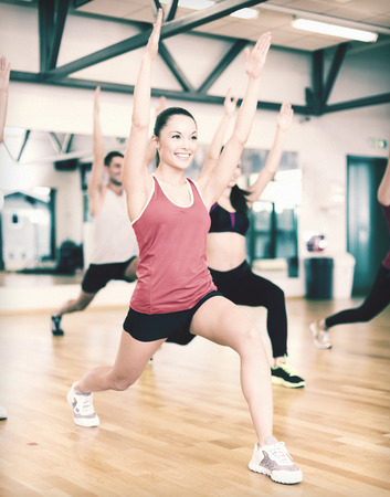 fitness, sport, training, gym and lifestyle concept - group of smiling people exercising in the gym photo