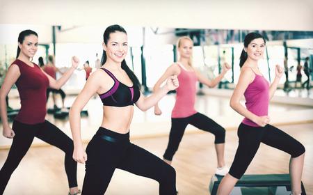 ejercicio aeróbico: fitness, deporte, entrenamiento, gimnasio y estilo de vida concepto - grupo de personas sonrientes que hacen aeróbicos