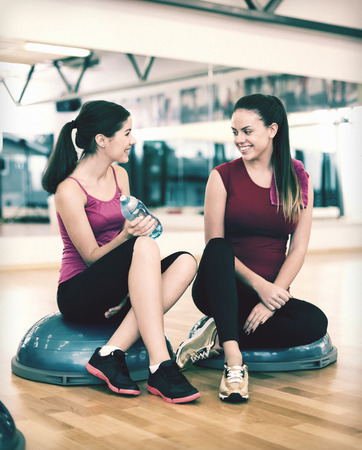 two and a half: fitness, sport, training, gym and lifestyle concept - two smiling women sitting on the half ball and relaxing after class in the gym