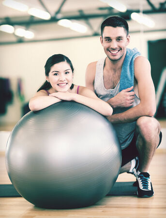 out of control: fitness, sport, training, gym and lifestyle concept - two smiling people with fitness ball in the gym