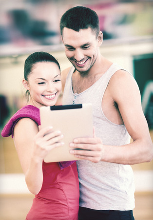 fitness, sport, training, gym and lifestyle concept - two smiling people with tablet pc in the gym photo