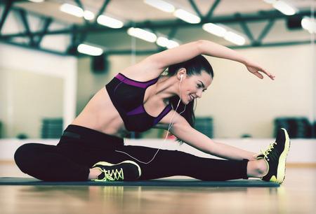 fitnes: fitness, sport, szkolenia, siłownia i koncepcja życia - rozciągając młoda kobieta z słuchawki na siłowni