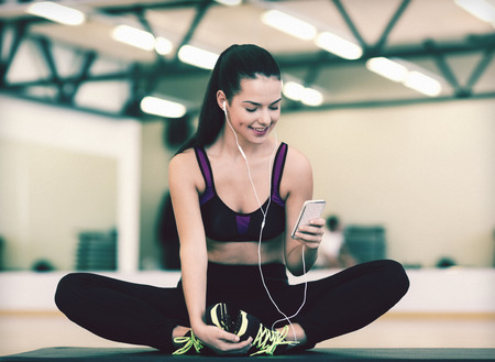 woman working out: fitness, sport, training, gym, technology and lifestyle concept - smiling woman with smartphone Stock Photo
