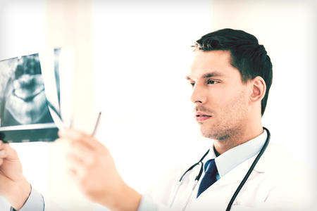 stomatologist: picture of male doctor or dentist looking at x-ray