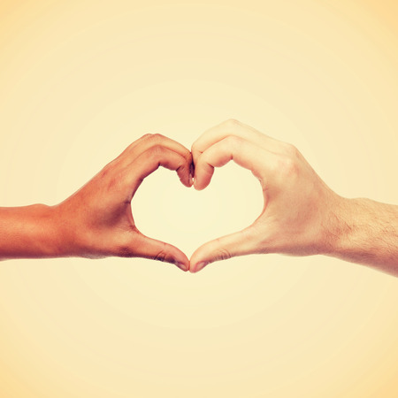 multiracial children: love and relationships concept - closeup of woman and man hands showing heart shape