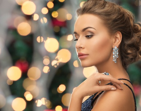 people, holidays and glamour concept - beautiful woman in evening dress wearing ring and earrings over christmas lights background 스톡 콘텐츠