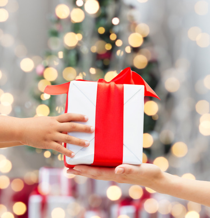 holidays, present, childhood and happiness concept - close up of child and mother hands with gift box over christmas tree lights background photo