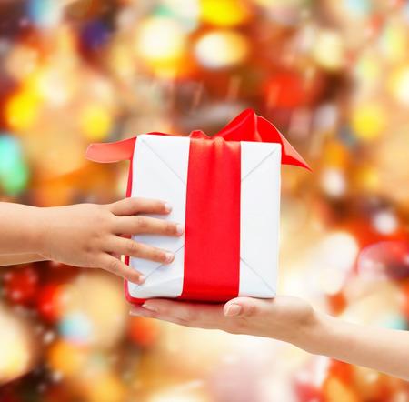 dar un regalo: días de fiesta, presente, navidad, la infancia y concepto de la felicidad - cerca de los niños y de manos de la madre con la caja de regalo sobre fondo rojo de las luces