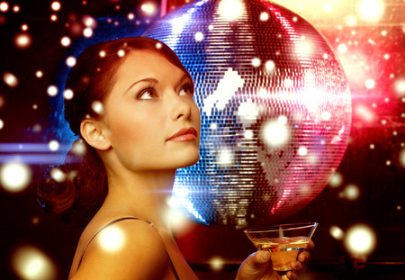 luxury, vip, nightlife, party, christmas, x-mas, new years eve concept - beautiful woman in evening dress with cocktail and disco ball photo
