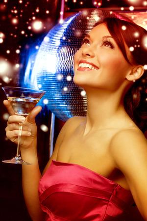 gente celebrando: lujo, vip, vida nocturna, fiesta, navidad, x-mas, concepto v�spera de a�o nuevo - hermosa mujer en traje de noche con un c�ctel y bola de discoteca