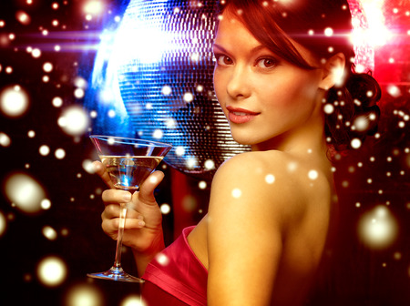 luxury, vip, nightlife, party, christmas, x-mas, new year's eve concept - beautiful woman in evening dress with cocktail and disco ball Foto de archivo