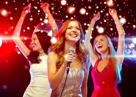 despedida de soltera: fiesta, año nuevo, celebración, amigos, despedida de soltera, cumpleaños concepto - tres mujeres en vestidos de noche bailando y cantando en el karaoke Foto de archivo